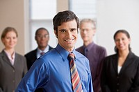 Businessman standing with coworkers in the background