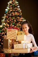 Hispanic girl holding gifts in front of Christmas tree