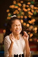 Hispanic girl with fingers crossed and eyes closed in front of Christmas tree