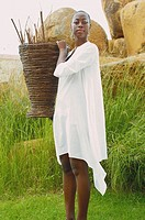African American woman carrying basket outdoors