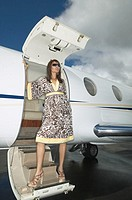 Woman standing in open door of small jet, Nobato, California, United States