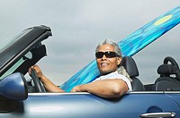 Senior man driving a convertible with a surfboard in it, Oakland, California, United States