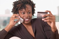 Young African woman on cell phone with credit card