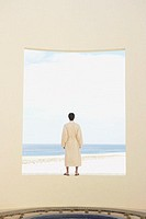 Person in robe looking out over the ocean, Los Cabos, Mexico