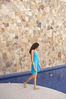 Woman walking next to hotel pool, Los Cabos, Mexico