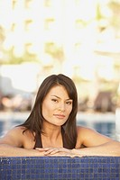 Hispanic woman leaning on the edge of a pool, Los Cabos, Mexico