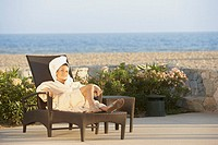 Woman in lounge chair at beach hotel, Los Cabos, Mexico