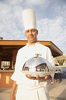 Hispanic male chef holding covered plate, Los Cabos, Mexico