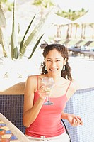 Hispanic woman with drink at hotel bar, Los Cabos, Mexico