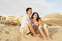 Couple sitting together on beach, Los Cabos, Mexico