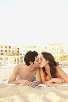 Couple lying on the beach kissing, Los Cabos, Mexico