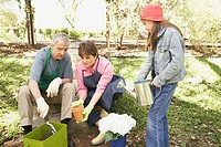 Hispanic grandparents and granddaughter gardening