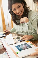Young Asian woman looking at scrapbook
