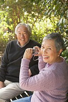 Senior Asian woman taking photograph of senior Asian man on a park bench, San Rafael, California, United States