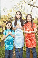 Three young Asian sisters holding fortune cookies, San Rafael, California, United States