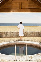 Woman in bathrobe outdoors at beach resort, Los Cabos, Mexico