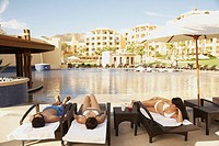 Group of friends relaxing next to a resort pool, Los Cabos, Mexico
