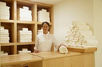 Spa employee behind counter with rolled towels, Los Cabos, Mexico