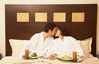 Hispanic couple eating in bed, Los Cabos, Mexico