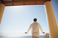 Man standing on balcony of resort hotel, Los Cabos, Mexico