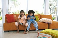Brother and sister (8-10) playing video game, smiling, portrait