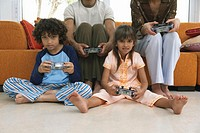 Parents with kids (8-10) playing video game, portrait
