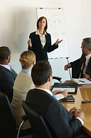 Businesswoman standing by flipchart in meeting, gesturing with hands