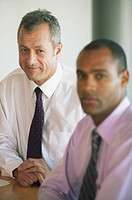 Two businessmen at conference table, portrait (focus on mature man)