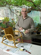 Senior man varnishing chair in greenhouse, smiling, portrait