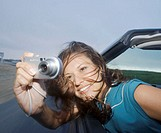 Young woman leaning out of convertible car, taking photograph