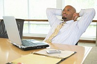 Businessman with laptop sitting in boardroom, hands behind head