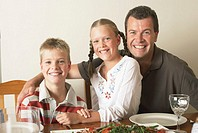 Father and twins (10-12) at dinner table, smiling, portrait