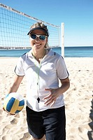 Young woman on beach holding volley ball, smiling