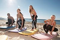 Four teenagers (16-18) in wet suits standing on surfboards on beach