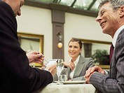 Businesspeople in restaurant smiling at man using electronic organiser