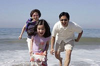 Grandmother, father and daughter (4-6) running on beach, smiling