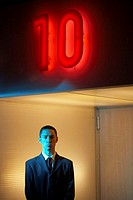 Businessman under neon ´10´ sign, portrait