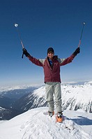 Male mountaineer with ski poles atop snowy peak, arms raised, portrait