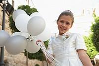 Girl (7-9) holding balloons, smiling, portrait