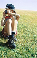 Girl sitting in grass, taking photo