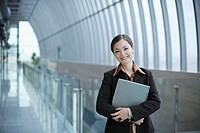 Businesswoman Standing in Corridor Holding Laptop