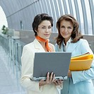 Businesswomen Using Laptop in Corridor