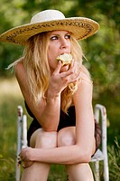 Young blonde woman eating apple sitting in green grass environment