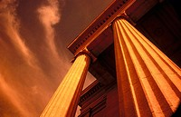 Architecture of two columns on building looking up at sky and clouds