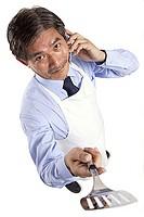 Mature man wearing apron, using mobile phone, holding spatula towards camera