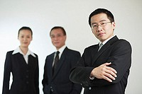 Young businessman with arms crossed, businessman and businesswoman in the background