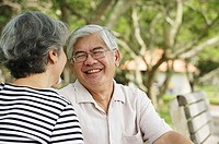Mature couple facing each other, man smiling
