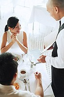 Waiter showing menu to couple at restaurant