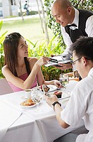 Couple in restaurant, woman giving credit card to waiter