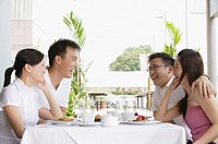 Group of friends at restaurant table, laughing